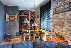 View over sofa backrest to dining area with wine rack and dartboard in open-plan interior with brick wall