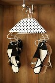 Wire coat hangers decorated with black and white polka-dot paper used to hang up lady's sandals