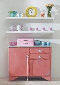 Battered pink kitchen cabinet below crockery on white floating shelves