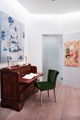 Upholstered chair at antique writing desk below painting on wall in modern interior