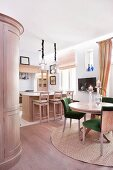 Dining table and chairs with green upholstery on round rug in front of island counter and bar stools made from pale wood