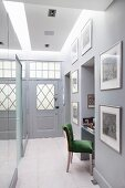 Narrow hallway with mirrored panels and workstation in niche with upholstered chair