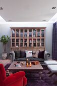 Suspended ceiling panel in lounge with various chairs, sofas and stools and glass-fronted cabinet in background