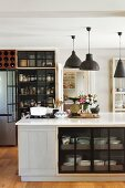 Island counter, charcoal pendant lamps and glass-fronted pantry cupboards in retro interior