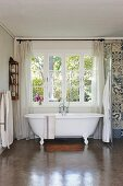 Vintage-style free-standing bathtub below lattice window