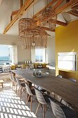 Enormous dining table in modern interior with exposed roof structure