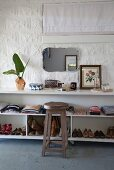 Wooden stool in front of clothing and children's shoes on shelves of white, open-fronted sideboard