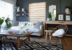 Rustic wooden coffee table on black and white patterned rug and sofa with scatter cushions in interior with dark wall