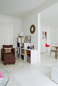 Leather armchair and low shelves in bright living room with open doorway leading to kitchen