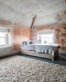 Child's bed with drawers below and pale grey blankets in purist, renovated attic room with patinated walls and ceiling