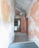 Corridor with different levels, niches and patinated walls in attic of old country house