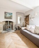 Sofa in front of log burner in old fireplace with antique mirror and stacked firewood in niches in comfortable lounge