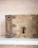 Rusty metal fittings on old piece of wood with keyhole against pale pink, patinated background