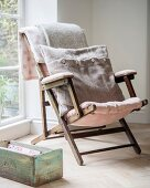 Vintage garden chair with dusky pink cushions and wool cushion and old wooden box on oak parquet floor
