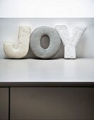 Decorative fabric letters spelling 'JOY' on pale grey surface