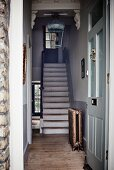 Wooden staircase in rustic foyer seen through front door