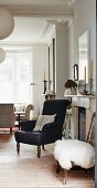 Black armchair and stool with white fur blanket next to open fireplace in traditional interior