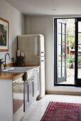 Simple kitchen counter and retro fridge-freezer next to open lattice door