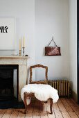 Vintage chairs with gilt wooden frame and white fur rug on seat next to fireplace