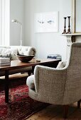 Armchair with ecru upholstery next to coffee table in traditional interior