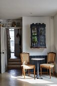 Two antique chairs around bistro table and small display cabinet above radiator next to open door with view into hallway