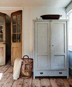 Simple wooden cupboard and basket in corner of room next to double doors