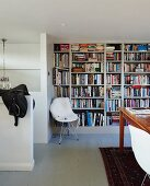 Classic shell chair with white fur blanket against bookcase in simple interior