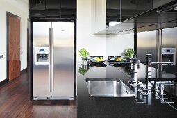 Black kitchen counter with stainless steel sink, glossy splashback and stainless steel fridge-freezer combination