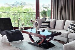 Dark couch and pale grey sofa set around Art Deco coffee table in front of glass wall with a view