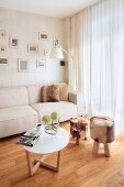 Round side table and stool with animal-skin cover in corner of bright living room