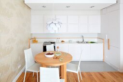 Round wooden table and white chairs in front of kitchen counter with white wall units