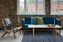 Classic-style armchair and wooden coffee table in front of sofa with blue cushions in loft-style interior