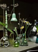 Various flowers in vases and turned candle in candlestick next to vintage, green pendant lamp