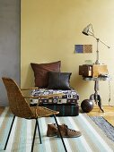 Wicker chair, floor cushions and lamp on retro side table