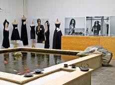 Grosses Wasserbassin mit Goldfischen im Atelier, im Hintergrund Schneiderpuppen mit eleganten, schwarzen Kleidern