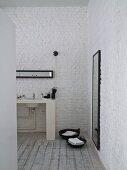 Bad Ensuite mit Waschtisch an geweisselter Ziegelwand, seitlich Körbe mit Handtüchern auf Dielenboden