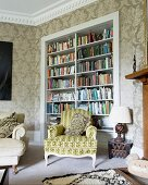Rococo armchair with patterned upholstery in front of bookcase in niche in corner of traditional living room with ornate wallpaper
