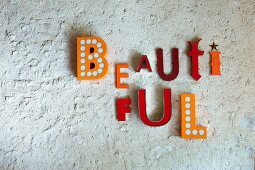 Message made from colourful decorative letters hung on stone wall