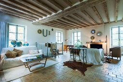 Wood-beamed ceiling and tiled floor in open-plan interior of rustic country house