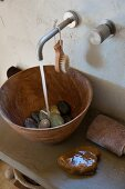 River pebbles in wooden sink on concrete washstand