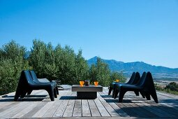 Modern seating group on wooden terrace surrounded by olive trees and fantastic panoramic view