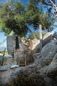 Outdoor shower behind stone wall and below olive tree growing on rocky slope