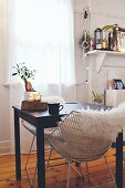 White fur blanket on retro chair at small black table below window