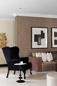 Black wing-back chair and side table next to sofa against wall with brown structured wallpaper