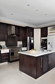 Island counter with dark-wood base units and white worksurface in open-plan designer kitchen
