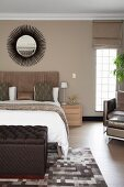 Dark brown ottoman at foot of double bed and sunburst mirror on beige-painted wall