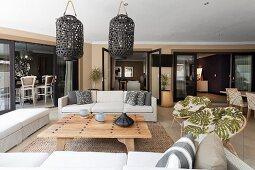 Sofa combination around wooden coffee table below dark, wicker, lantern-style lamps in spacious interior