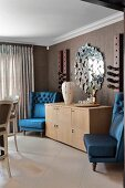 Armchairs with shiny blue upholstery flanking pale wooden sideboard in traditional interior