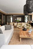 Lounge area with pale sofa, coffee table and lantern-style mesh pendant lamps in open-plan interior