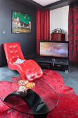 Glass coffee table in front of easy chair with red leather cover; TV on floor in background